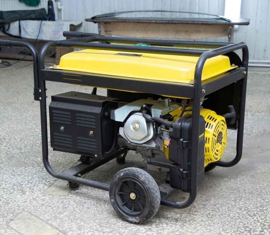 A yellow portable generator sitting on the concrete outside of a building.
