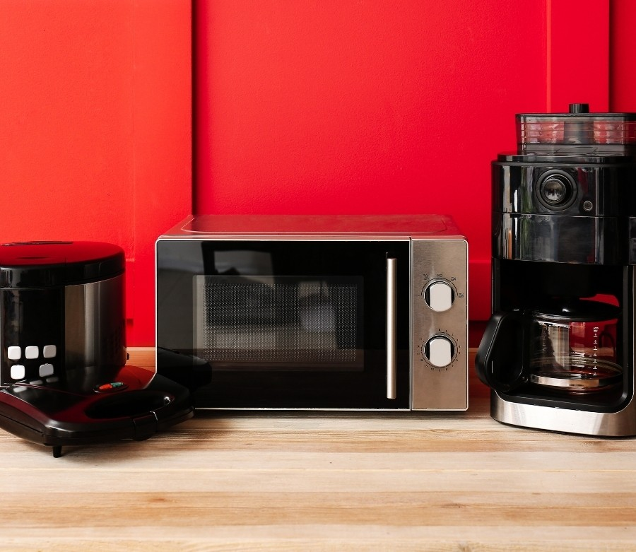 A waffle maker, toaster oven, and coffee maker in front of a bright red wall.