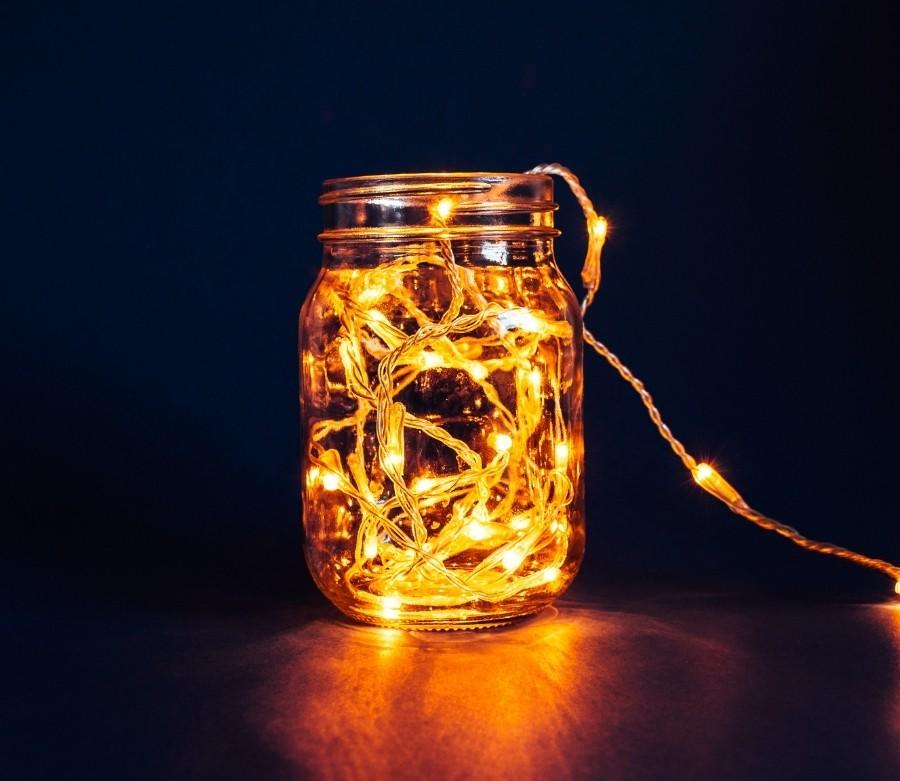 Warm white lights in a mason jar against dark background.
