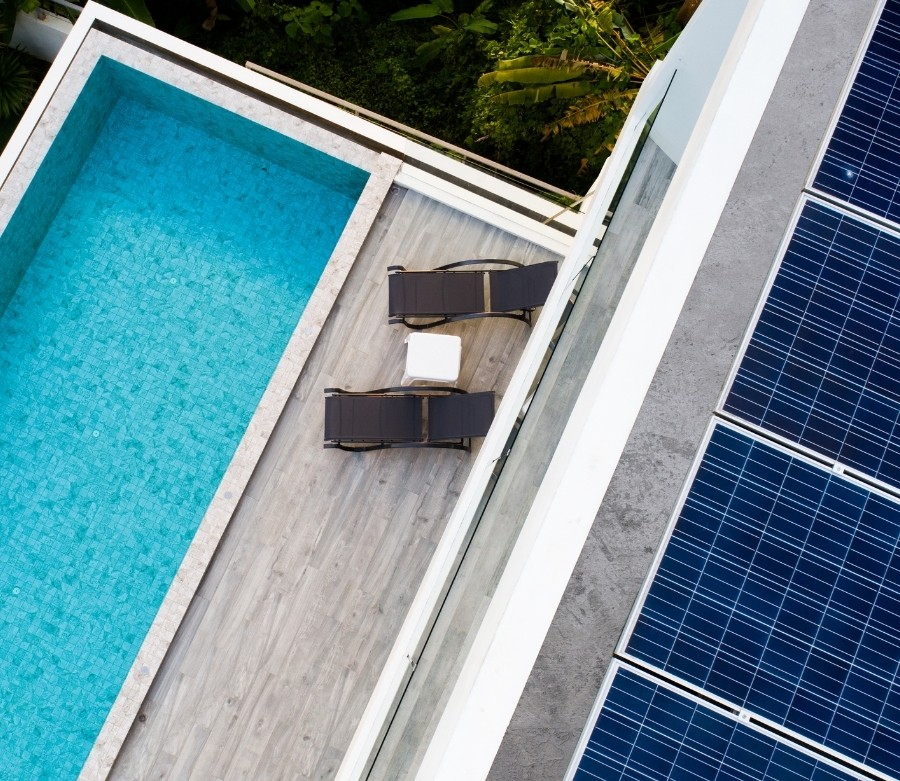 Aerial view of a narrow rectangular swimming pool and solar roof panels.