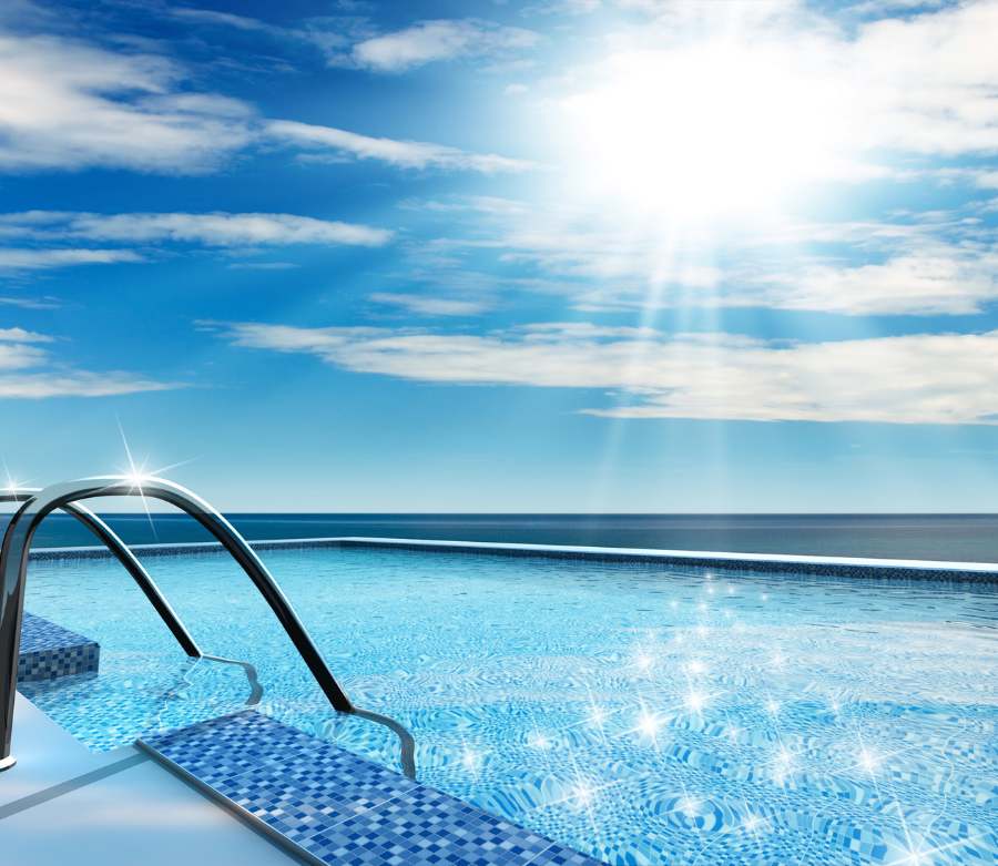 A luxury swimming pool with sunlight sparkling on the water and the ocean in the background.